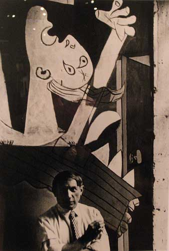 Pablo Picasso in front of his painting Guernica