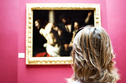 "woman looking at a caravaggio is like ""kidnapped"" by the composition of the painting"